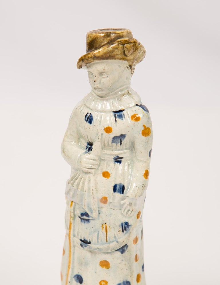 A pair of early Prattware figures, made in England circa 1800, these naive figures were deaccessioned from Colonial Williamsburg (each figure has its cat # in red ink on the inside). The potters relatively incompetent representations result in a