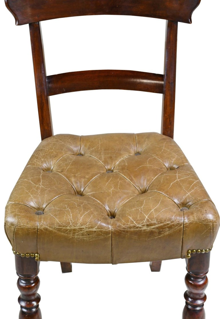 A pair of early Victorian side chairs in mahogany with curved top rail, and raised on turned front legs and saber back legs. Seat is upholstered in a tufted, beige/camel-colored leather with brass nailheads, England, circa 1840.   Measures: 18