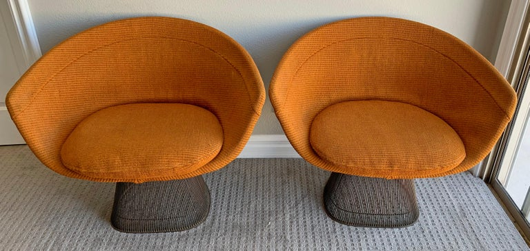 An absolutely wonderful pair of Warren Platner bronze lounge chairs. These early lounge chairs feature their original orange nubby upholstery, original tags (on both chairs) and original stickers that read