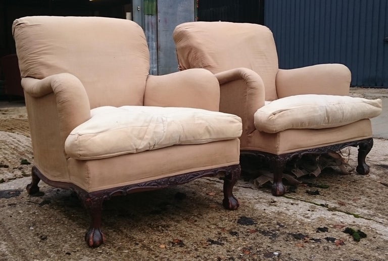 A very rare pair of Howard and Sons chairs standing on ball and claw feet. These chairs are large and comfortable. They are stamped Berners Street which is the earlier and most desirable period for these comfortable chairs. There is some writing on