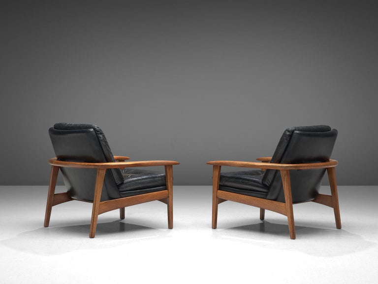 Pair of easy chairs, black leather and teak, Denmark, 1960s.  This set of easy chairs features a teak frame with a tufted seat and back. The chairs have a sturdy frame showing refined craftsmanship, holding a comfortable leather shell. The tufted