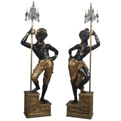 Pair of Ebonized and Gilt Figures Supporting Three-Light Candelabra, circa 1920