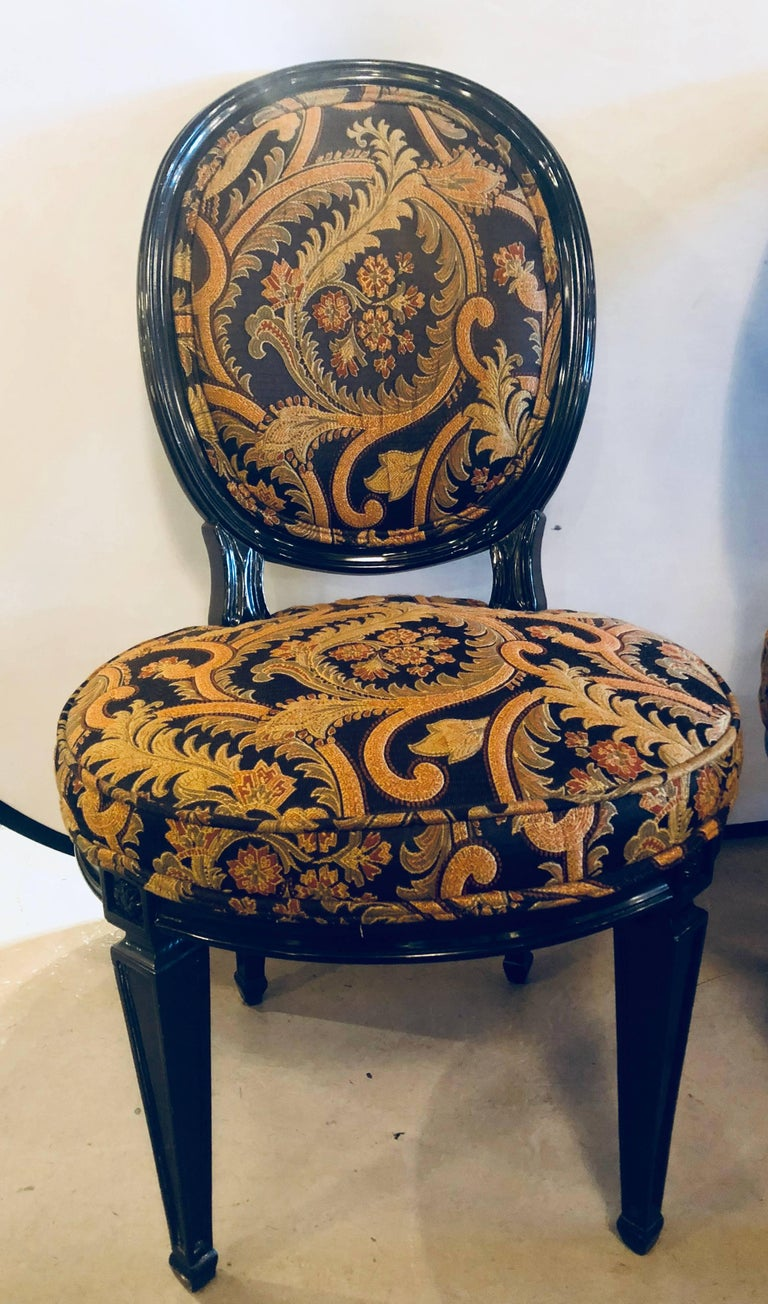 Pair of ebonized Louis XVI style side or office chairs beautifully upholstered. This solid wood pair of chairs depict the Hollywood Regency eras flair for glamour and style at its peek.