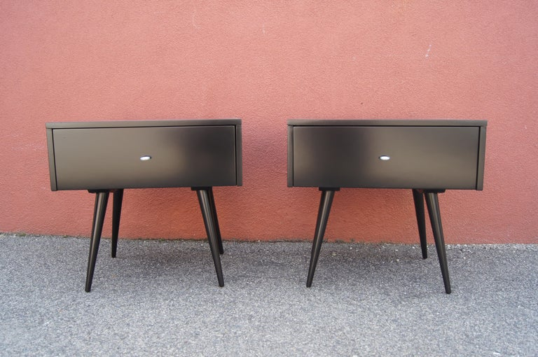 Paul McCobb designed this pair of side tables, model 1540, for Winchendon's Planner Group. An ebonized maple case sits on angular tapered legs; its single wide drawer sports an aluminum ring pull. The tables work equally well as nightstands.