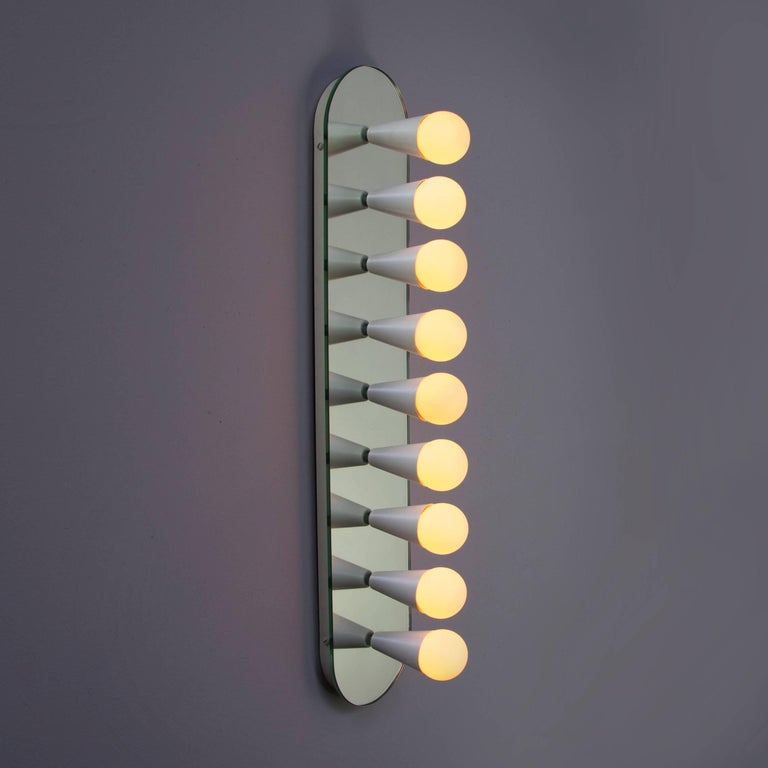 Simple, elegant and playful, the Echo series is a line of surface-mount fixtures that can be used on a wall or ceiling. White or brass cones mount to mirrored glass to perfectly reflect each bulb, giving the illusion of lights floating in
