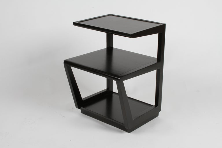 Pair of Drexel Precedent collection three-tiered end tables or nightstands designed by Edward Wormley, top shelf covered in leather, circa 1949. Silver elm is refinished in dark espresso. One table has the stencil to the underside, with