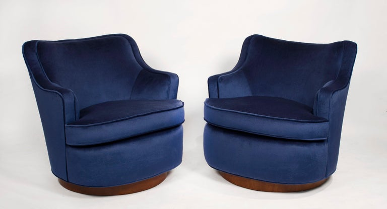 Early pair of Dunbar swivel chairs fully restored in high grade blue velvet. New foam and hand tied springs. These are extremely comfortable even for a tall person and are very high-quality construction with solid hardwood frames.