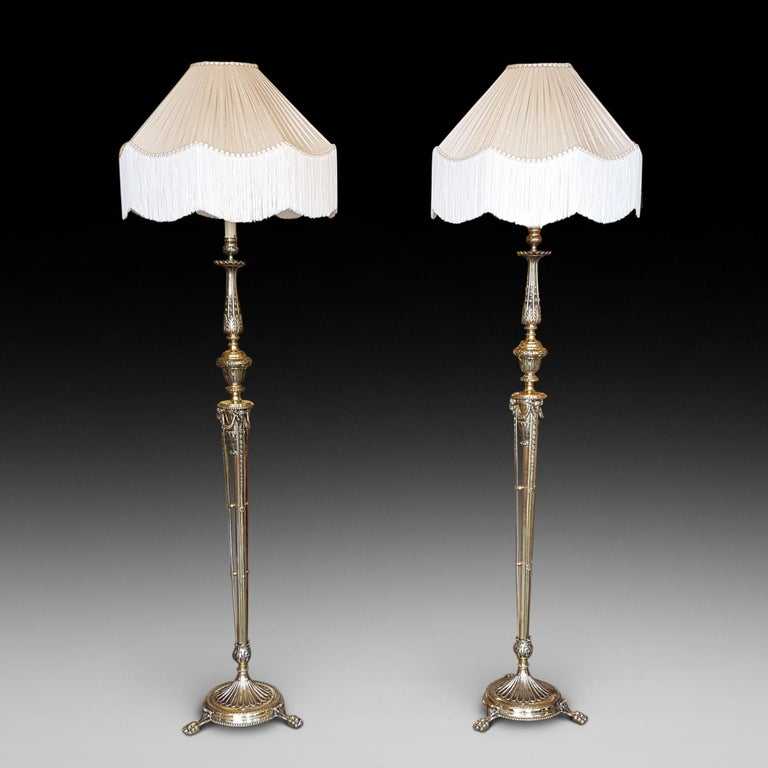 Pair of Edwardian Adam style brass lamp standards, each with bellflower and stiff leaf decoration and with rams heads to each vase support, raised on a circular base with paw feet, the lampshade(s) are newly handmade silks by the same maker as