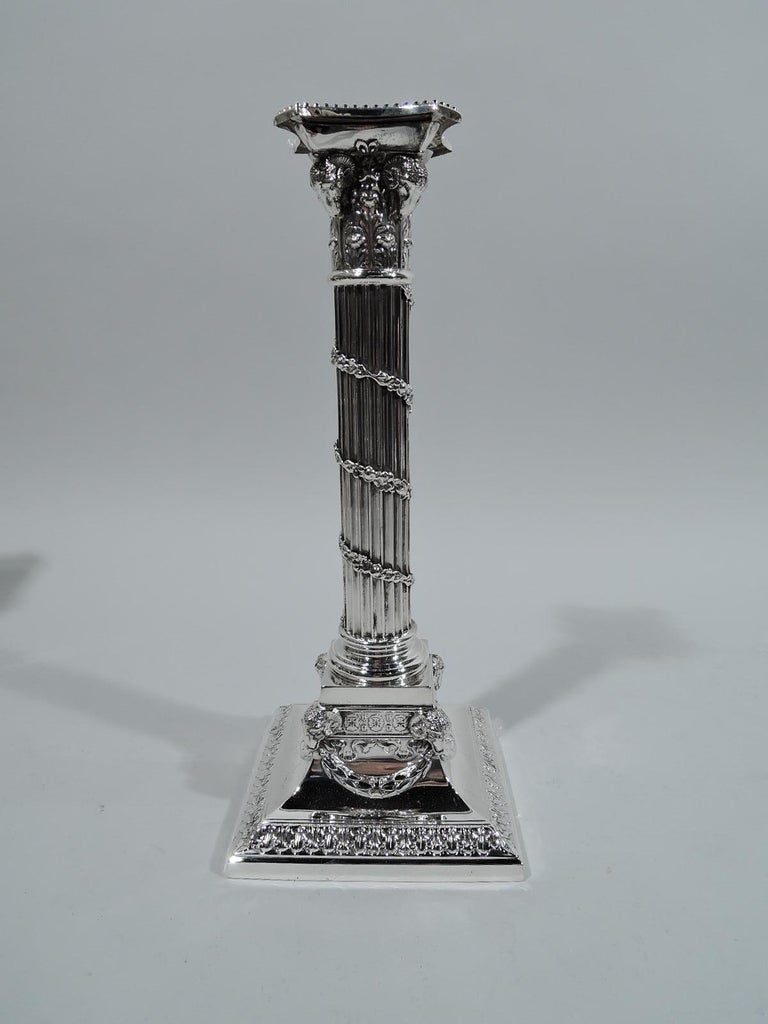 Pair of Edwardian neoclassical sterling silver candlesticks. Made by Mauser in New York, circa 1910. Each: Fluted column with descending wraparound garland. Composite Corinthian capital with ram's heads. More ram's heads applied to square base