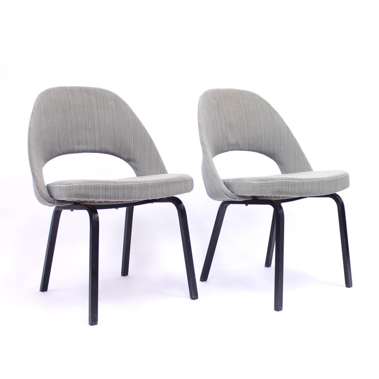 Pair of Eero Saarinen executive chairs by Nordiska Kompaniet under license from Knoll International Ltd. These examples were produced in 1962. They still have their original grey/black/green striped fabric on the back and seat. Black lacquered metal