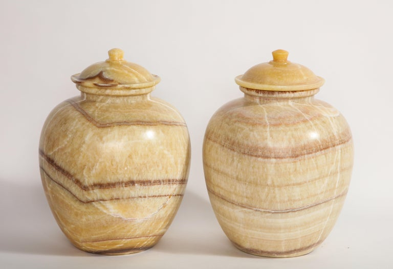 A beautiful and quite decorative pair of midcentury/Art Deco style Egyptian honey alabaster marble covered vases. Each is beautifully hand carved with gorgeous white, honey-yellow, and deep purple juxtaposing striations. These look fantastic in any