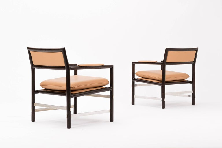 Edward Wormley Janus Collection for Dunbar. Solid oak frames with stainless steel stretchers that connect the legs. The chair have their original finish and have been reupholstered in spinneybeck leather. Four pairs available.