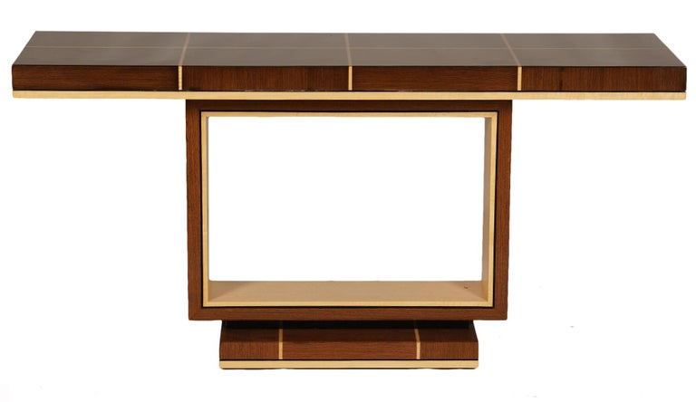The console table features  a long top divided into rectangles by light cored stripes of inlay resting on an upright rectangular two color frame sitting on a square base that repeats the top's pattern.