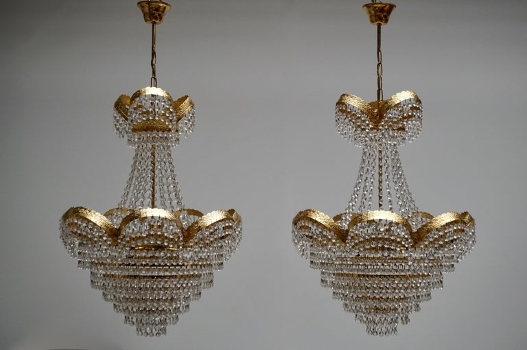 One Elegant crystal and brass chandelier from the 1950s-1970s. Please note that price is per item not for the set. Measures: Diameter 50 cm. Height fixture 65 cm. Total height including the chain 90 cm. The light requires six single E27 screw fit