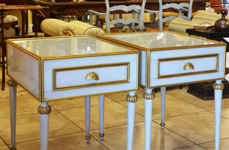 This unusual pair of French Louis XVI style milk glass mounted one drawer side tables feature bodies mounted with giltwood edged milk glass on top and sides resting on four round tapering legs with giltwood accents. The likely date to the