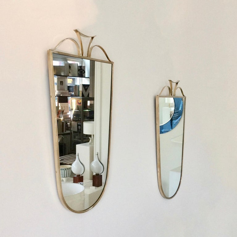 Very elegant pair of wall mirrors, circa 1950, Italy. Brass and mirrored glass, possibly produced by Fontana Arte. Good original vintage condition, nice quality.