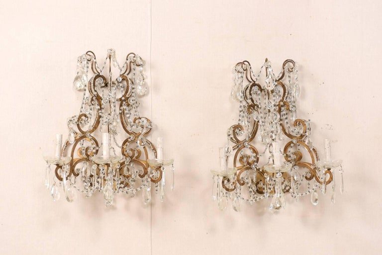 A pair of Italian mid-20th century crystal three-light wall sconces. This pair of Italian crystal sconces from the mid-20th century features a variety of faceted crystals ornately decorating the scrolled and gilded metal armature and arms. Strands