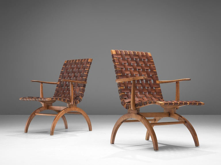 Pair of Spanish armchairs, elmwood and patinated leather, Spain, 1960s  A pair of Spanish midcentury leather strap armchairs in patinated cognac leather with woven seats. The wonderfully carved wood bases are slim and elegant, which reminds of the
