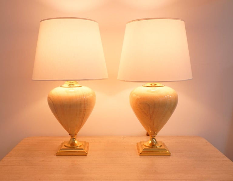 Beautiful pair of table lamps by Maison Le Dauphin, France, circa 1970s. Brass base and ceramic body in caramel color. Good condition with small stains on the base (picture).  Dimensions: Height 29.23 in. (74 cm), diameter 17.32 in. (44 cm).