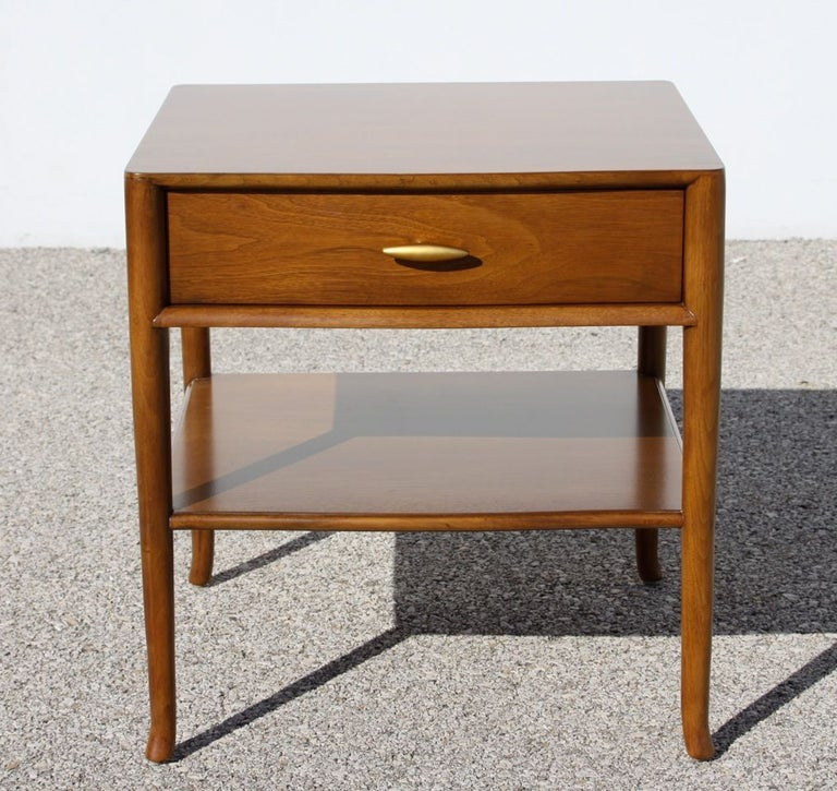 Pair of elegant and not often seen T. H. Robsjohn Gibbings nightstands for Widdicomb, dated 1955, label, walnut with restored original finish on splayed legs drawers having 24-karat gold porcelain handles. Tops always had glass, glass tops included,