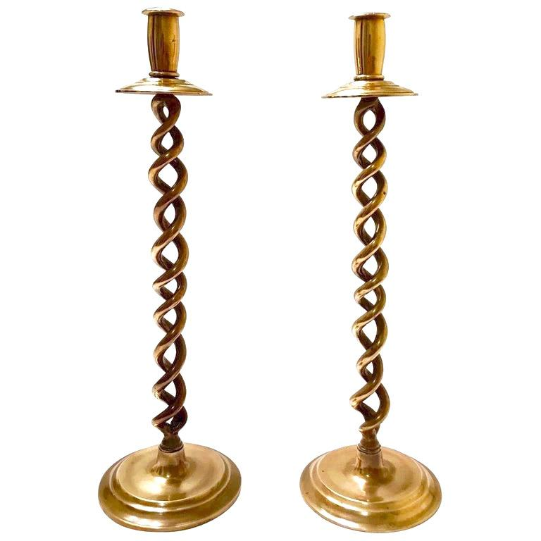 Pair of Mid-Century Modern candlesticks with Victorian Revival design. Beautiful candleholders in cast polished brass with braided stems or barley twist design. The candle holders have circular stepped bases and have solid weight to the touch. Minor