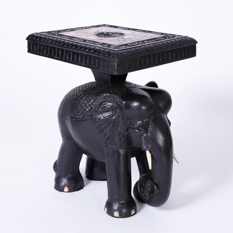 Exotic pair of end tables or stands each with floral bone inlays on rosewood tops and ebonized hand carved borders on carved wood elephant bases with bone tusks.