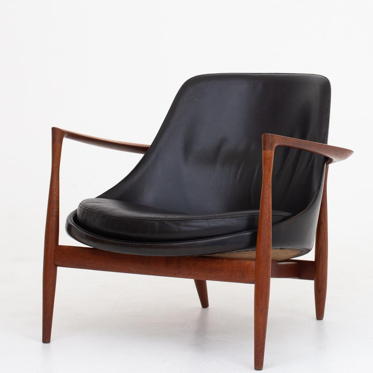 U56, pair of 'Elizabeth' easy chairs in teak and patinated black leather. Designed in 1956. Marked by maker Christensen & Larsen.
