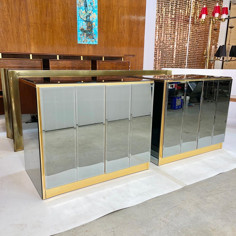 Pair of mirrored cabinets or oversized nightstands by O.B. Solie for Ello Furniture Manufacturing Corp. clad on four sides in beveled blue/grey smoked mirror and trimmed in brass and brass anodized aluminum. Both have double doors with magnetic