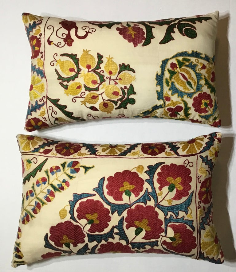 """Beautiful pair of pillows made of hand embroidery silk on cream color background, vebrent colors of red, green, indigo and gold, of exceptional motif or vines flowers and pomegranates. Fine cotton backing with fresh new inserts. Sizes: 24"""" x 14"""" x"""