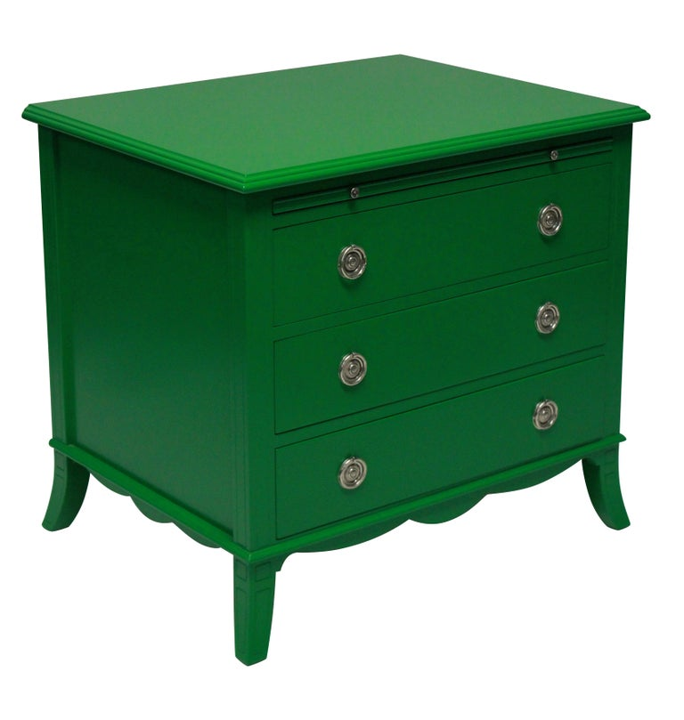 A pair of chests in green lacquer in the manner of Dorothy Draper, each with three drawers and a deep leather brushing slide. The handles of silver plate and good quality.