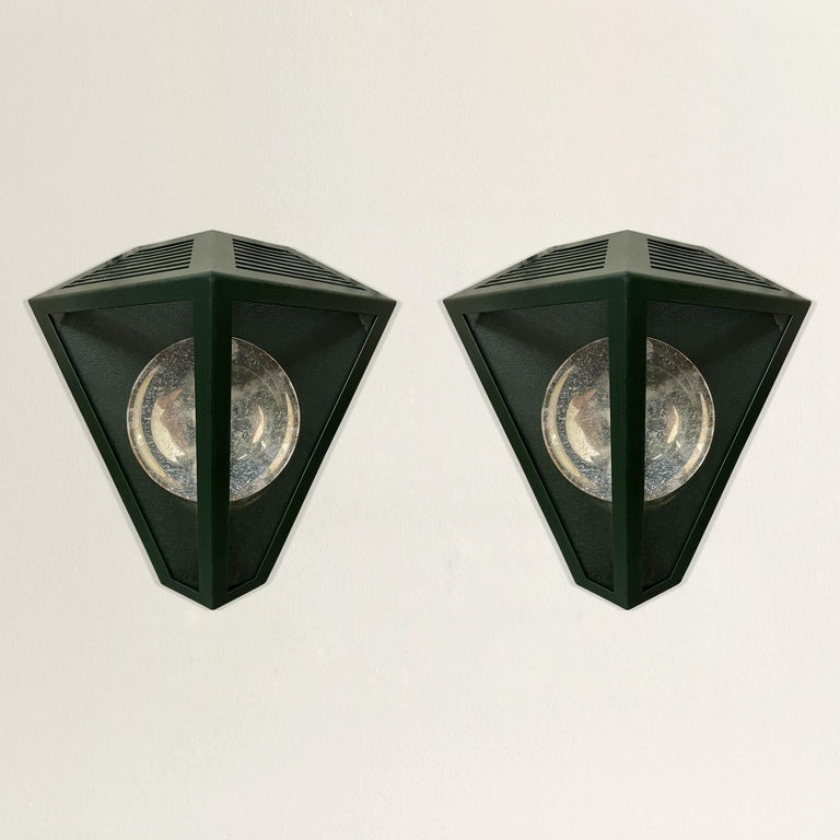 A striking pair of late 20th century American wall lanterns with a sophisticated emerald green painted finish, and silver-plated reflectors. Wired for US; candelabra bulbs.