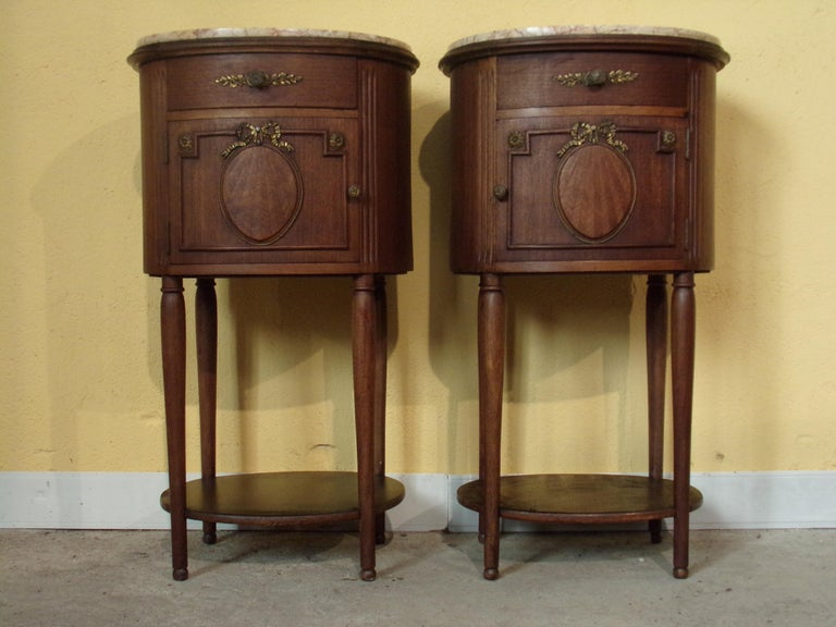 A stunning pair of oval mahogany veneered and inlaid Empire style bedside cabinets with Ormolu mounts and Satinwood Harewood and box wood inlay C1920 with rose veined Italian marble tops.