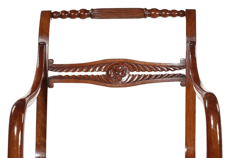 The reeded and turned toprails above lateral and leaf carved cross bars, with overswept arms, on caned seats with square tapering downswept legs, together with squab cushions, each 56cm wide, 47cm deep, 87cm high. (2).