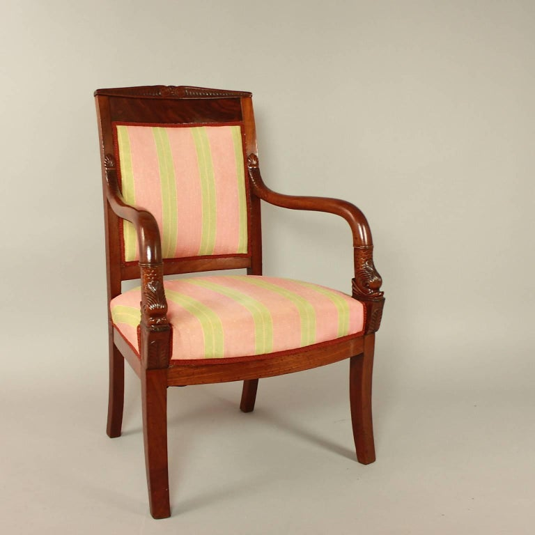 A pair of Empire mahogany fauteuils or armchairs 'aux Dauphine'' in the manner of Pierre Bellange (1760-1844). The mahogany frame with sabre front legs continuing as arm supports, the back legs raked. The arms curved and carved with a mythological