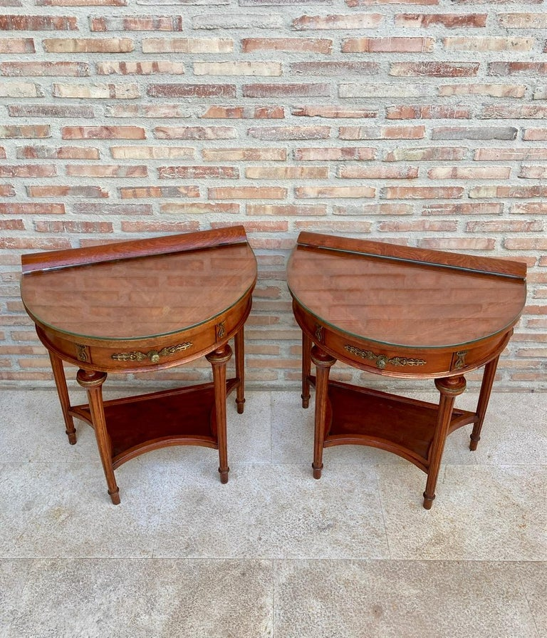 Beautiful pair of 1930s empire style mahogany nightstands.  They are shaped like a half moon and two legs give elegance and typical style of their time. They also have a central drawer ideal for storing small items.  It also has a very practical