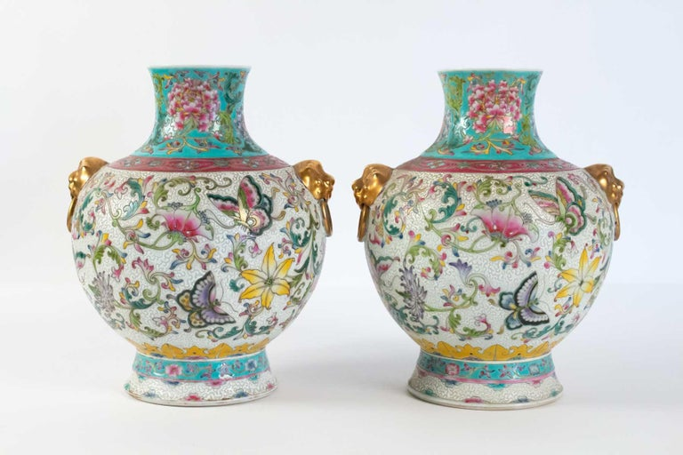 Pair of glazed porcelain vases, China, works of art, Decor of butterflies among the flowers, shaped heads of golden lions. Apocryphal mark on the back, China, Republic Period.