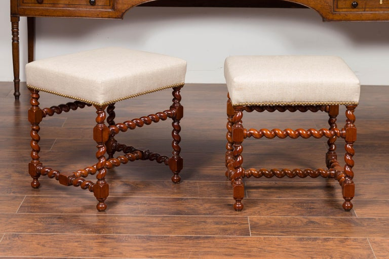 A pair of English walnut stools from the mid-19th century, with barley twist base and new upholstery. Born in England during the third quarter of the 19th century, each of this pair of walnut stools features a rectangular seat newly recovered with a