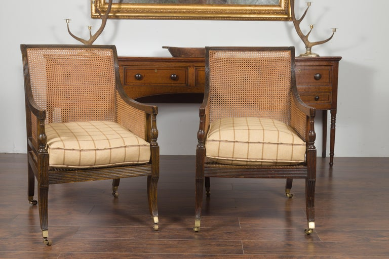 A pair of English oak library chairs from the late 19th century, with cane and custom cushions. Created in England during the third quarter of the 19th century, this pair of cane and oak library chairs features out-scrolling backs flowing seamlessly