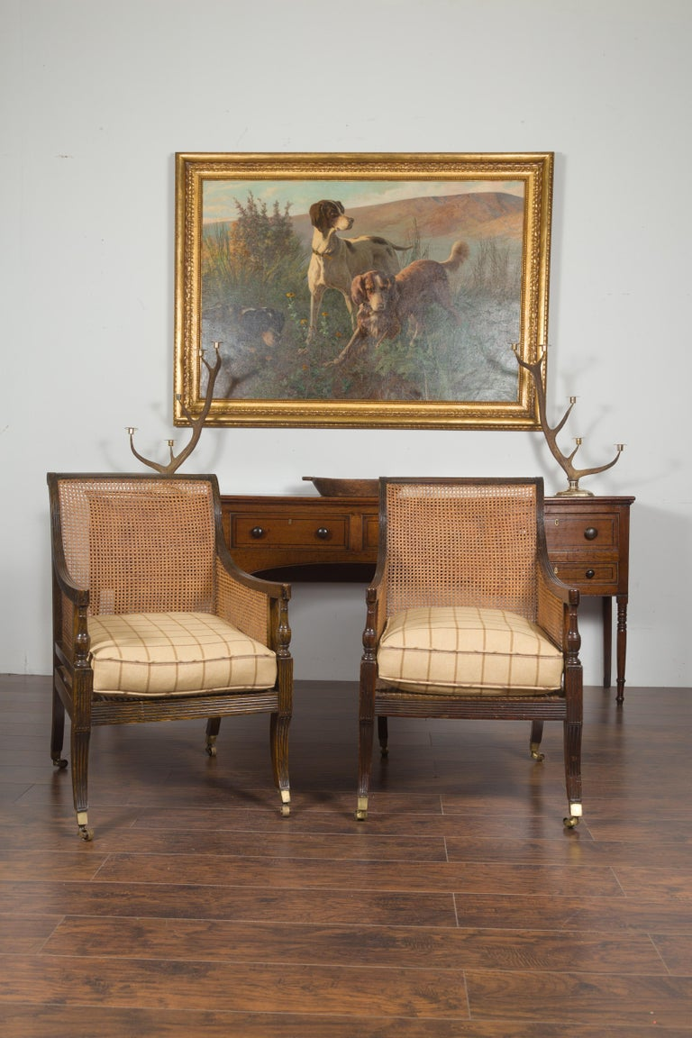 Pair of English 1870s Cane and Oak Library Chairs with Cushions and Casters In Good Condition For Sale In Atlanta, GA