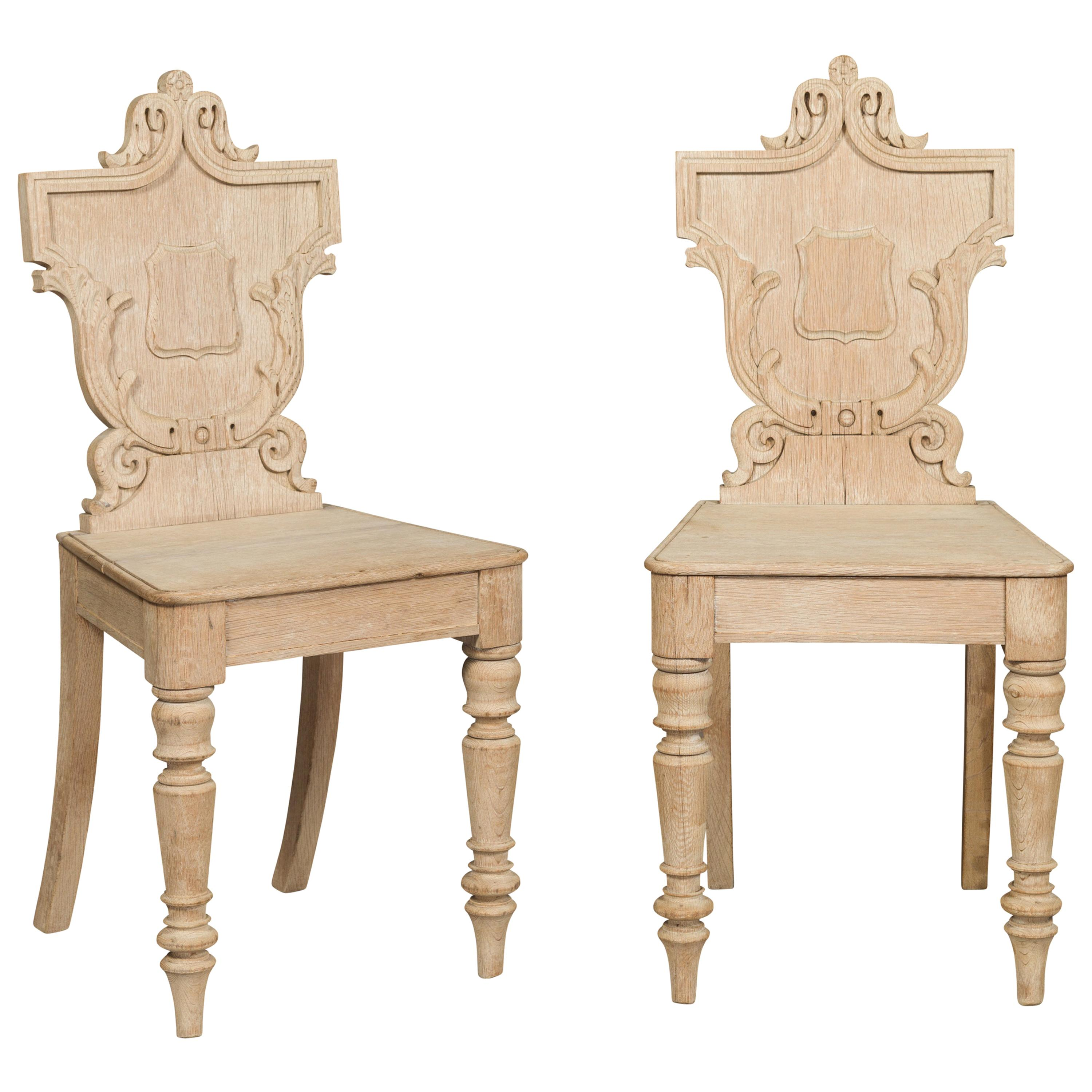 Pair of English 1880s Bleached Oak Hall Chairs with Shield-Shaped Carved Backs
