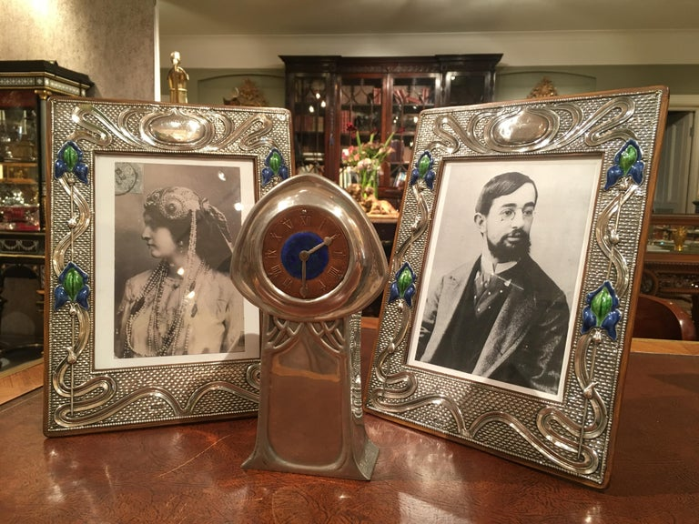 A pair of silver photograph framesof the Art Nouveau period.  Both being Hall Marked for Chester 1905, having the touch mark of J&R Griffin; the silver having embossed sinuous designs and dressed with turquoise enamelled cartouches, circa