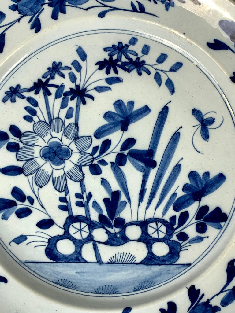 We are pleased to offer this pair of blue and white Delft chargers made in England circa 1760. They are hand-painted in a beautiful soft cobalt blue showing traditional decoration: an oversized flower, a butterfly, and pierced rocks. The border of