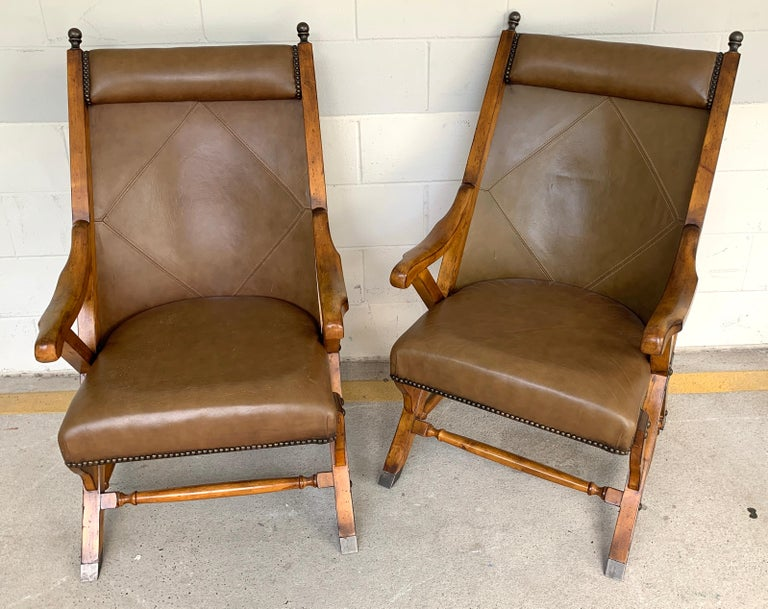 Pair of English Campaign style chair elm and leather chairs, Each one with stitched leather backrests, raised on stationary (they do not fold) brass-mounted elm frames. 24