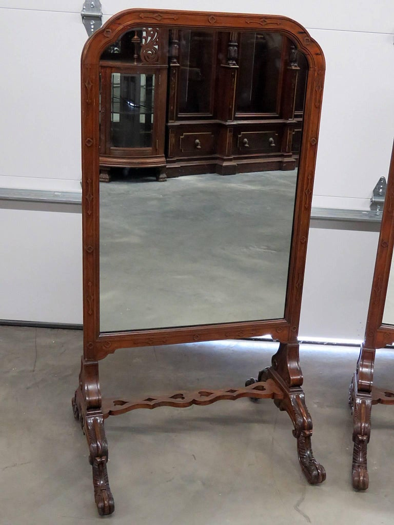Pair of English early 20th century carved walnut standing mirrors.