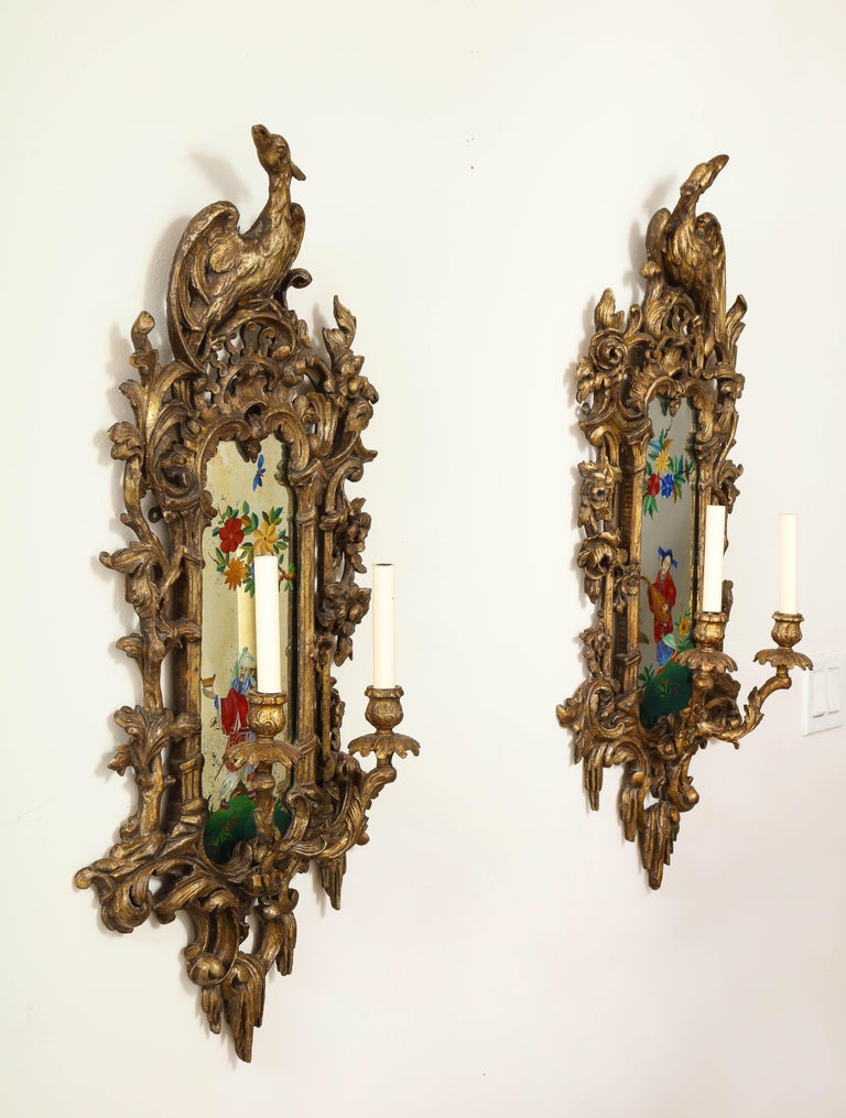 A fantastic pair of English chinoiserie painted reverse on glass, carved giltwood mirrored two-light sconces. Each is beautifully hand carved and gilt in a gorgeous gold finish with fabulous hand carved open-work and two mirror-image giltwood birds