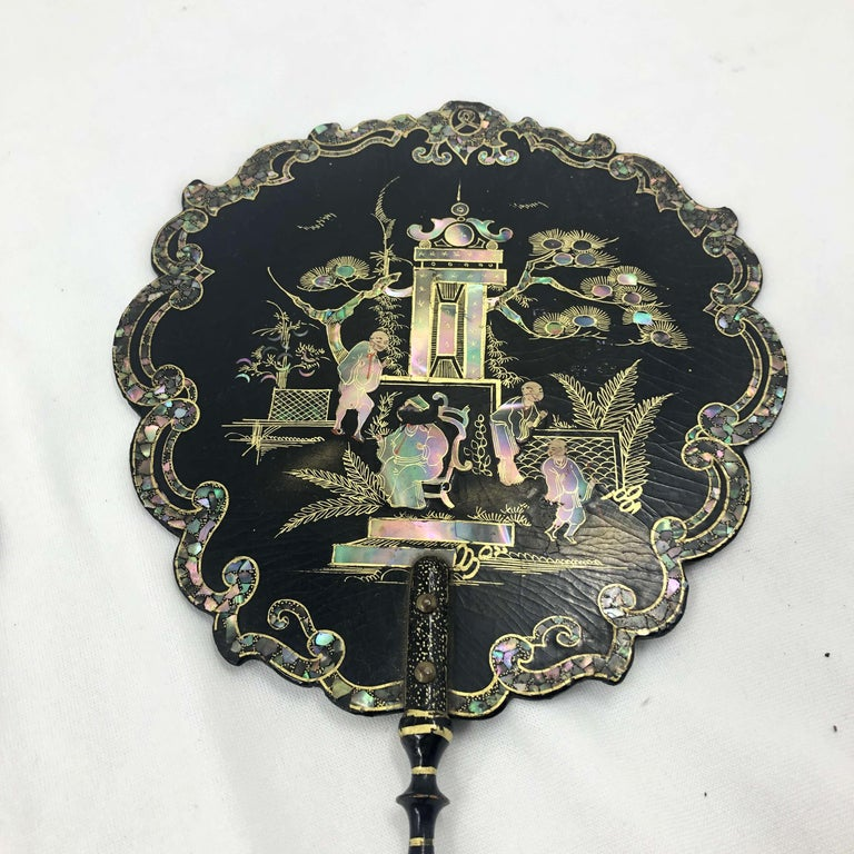 A pair of Victorian mother of pearl inlaid scalloped lacquered and chinoiserie decorated hand held fans with turned handles and gilt decorations.
