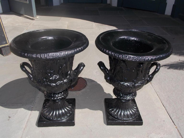 Pair of English figural frieze cast iron powder coated Charleston green campana-form urns with flanking side handles, and terminating on circular fluted squared plinths.  Late 19th century. Measures: 20 Tall / 15 Diameter top / 8.5 squared base.