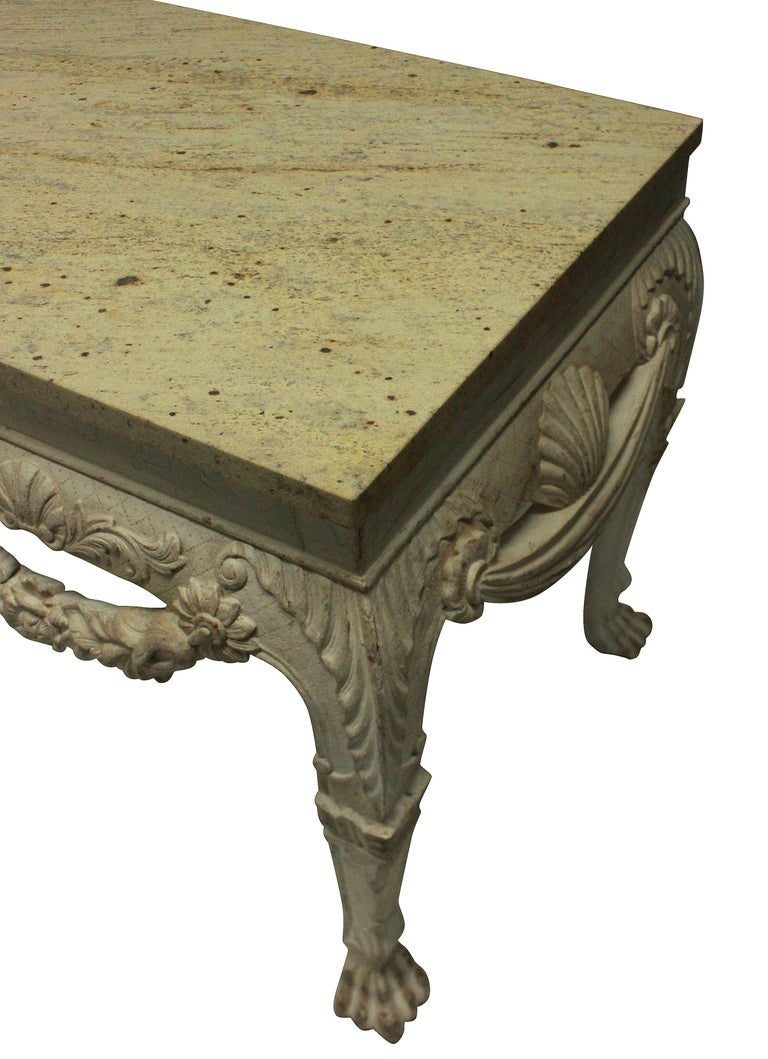 A large pair of English country house console tables in the 18th century manner, with lion masks, swags and acanthus carvings. Distressed painted mahogany with stone colored marble tops.