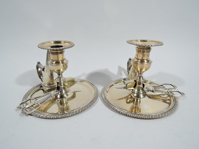 Pair of George III gilt sterling silver chambersticks. Made by Thomas & George Hayter in London in 1819. Each: Campana socket on spool foot mounted to open base inset with wick cutters. Round wax pan with capped flying scroll handle holding conical