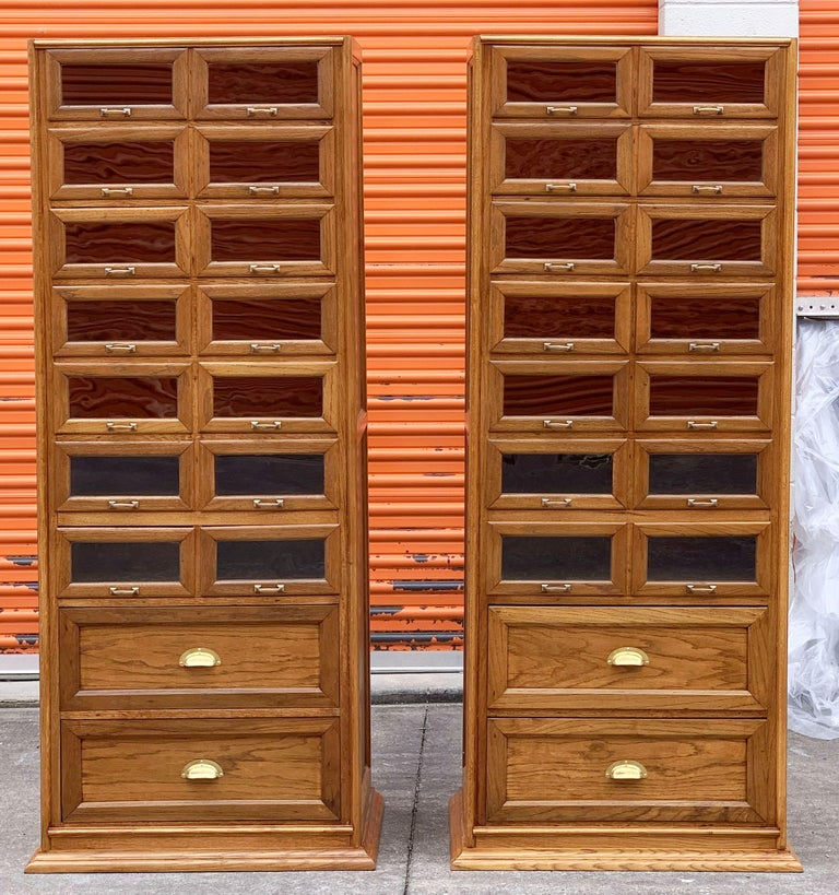 An exceptional pair of large haberdashery or haberdasher's cabinets from England - each featuring:  14 glass fronted drawers over two cupboard drawers, 16 drawers total on each industrial style cabinet.  The fitted drawers with handsome brass